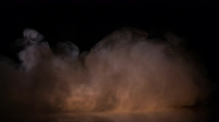 title : Clouds of moving heavy fog in orange light spot on black background