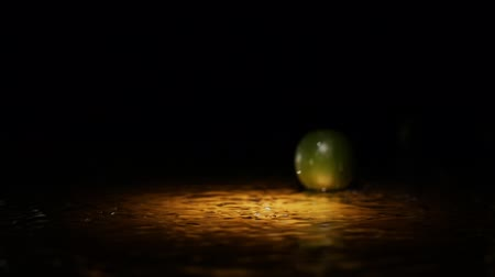 cítrico : Fresh citrus fruits lime falling on water surface in light spot with liquid splash and droplets in slow motion