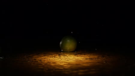 calcário : Fresh citrus lime falling on wet surface with lot of splashes and drops in orange light spot black