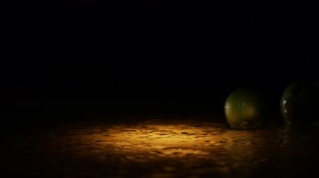 césar : Fresh limes falling on water surface in light spot with liquid splash and droplets in slow motion