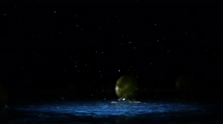 cítrico : Lime citrus fruits falling on water surface in blue light spot with liquid splash and drops in slow motion