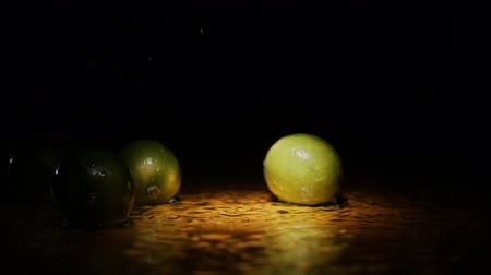 cítrico : Limes falling in water surface in light spot and black background in slow motion