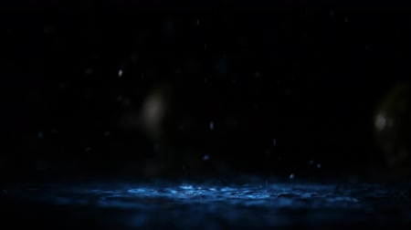 ミント : Limes falling on water surface in blue light spot with liquid splash and drops in slow motion close up