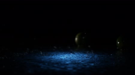 tonikum : Limes falling on water surface in blue light spot with liquid splash and drops in slow motion