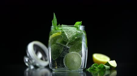 лимонный : Mojito cocktail citrus lemonade with lime lemon and mint in cold sparkling soda water prepared for drinking