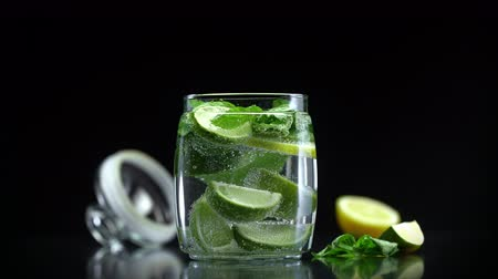 cítrico : Mojito citrus lemonade with lime lemon and mint in cold sparkling soda water prepared for drinking on black background Vídeos