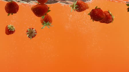 плодоношение : Fresh strawberry fall into water on orange background. Summer berries in liquid Стоковые видеозаписи