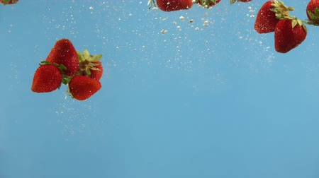 плодоношение : Fresh strawberry fall into water on blue background. Summer berries in liquid