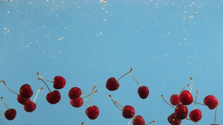 zöldségbolt : Ripe cherry fall into water on blue background. Red berry cherries in liquid