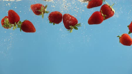 frutoso : Ripe strawberries fall into water on blue background. Summer berry in liquid