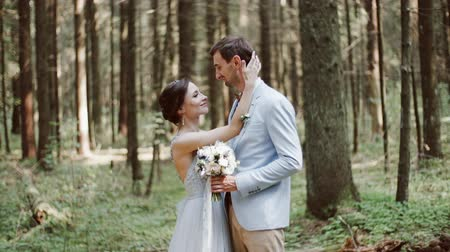 örökkévalóság : Bride and groom embrace one another and smile standing in pine forest wedding Stock mozgókép