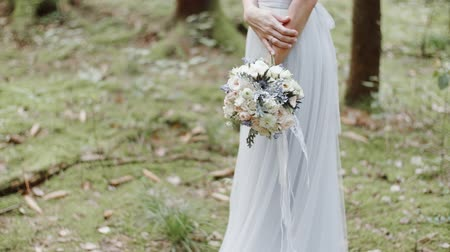новобрачный : Bride with wedding bouquet of flowers standing on moss in pine forest