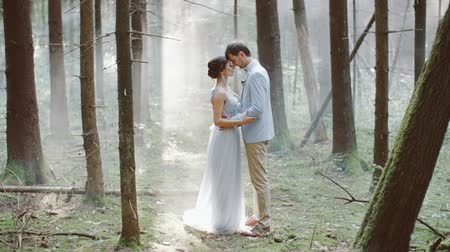 новобрачный : Married couple bride groom embrace standing in forest fog on background wedding