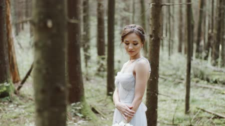 örökkévalóság : Portrait of bride with wedding bouquet standing on moss in pine forest Stock mozgókép