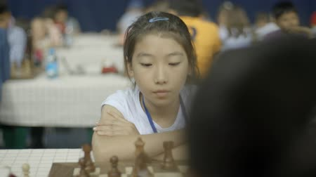 przedszkolak : Minsk, Belarus - June 22, 2018. Portrait of asian girl playing chess