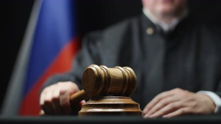 tribunal : Judge hammering with wooden gavel against Russian flag in court room Stock Footage