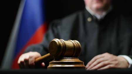 tribunal : Judge with gavel in hand hammering against Russian flag in court room