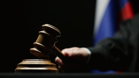 cold war : Judge with gavel in his hand hammering against Russian flag in courtroom