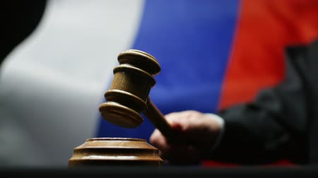 tribunal : Judge with gavel in his hand hammering against waving Russian flag courtroom