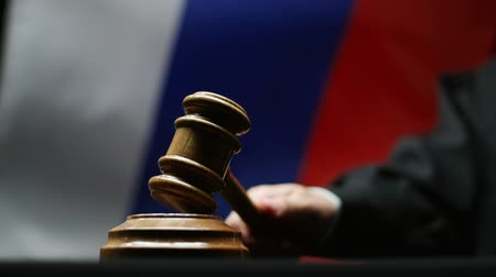 judiciary : Judge with gavel in his hand against waving Russian flag in courtroom