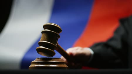 judiciary : Judge with gavel in his hand against waving Russian flag in court room