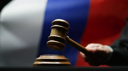 tribunal : Judge with hammer in his hand against waving Russian flag in court room Stock Footage