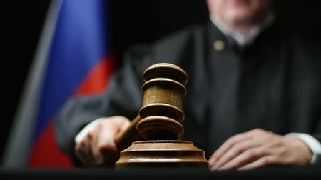 tribunal : Judge with hammer in his hand against Russian flag in court room