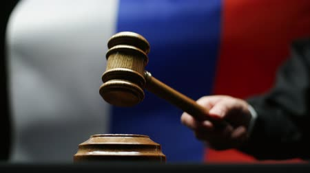adli : Judge with gavel in his hand hammering against waving Russian flag in courtroom Stok Video