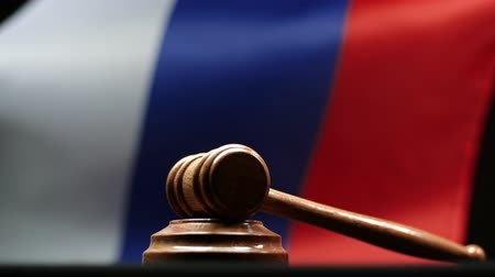 cold war : Judges wooden gavel on block against Russian flag waving Federation court room