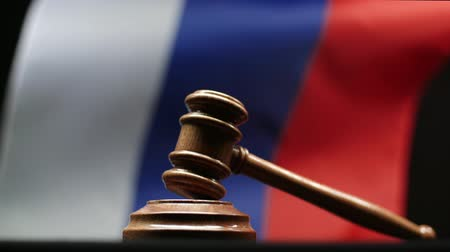 tribunal : Judges wooden gavel on block against Russian flag waving in court Stock Footage