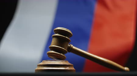cold war : Judges wooden hammer against Russian flag waving. Gavel on block court room Stock Footage