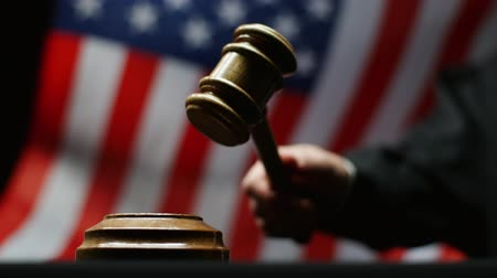 judiciary : Judge hammering with wooden gavel against waving American flag in USA court room