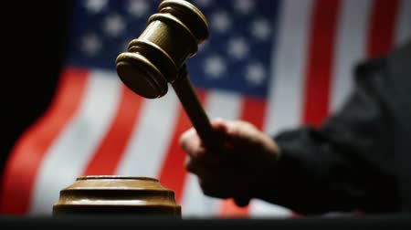 tribunal : Judge hammering with wooden gavel in hand against waving American flag in court