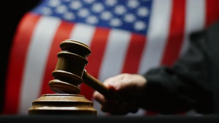 judiciary : Judge with hammer in hand against waving American flag in United States court Stock Footage