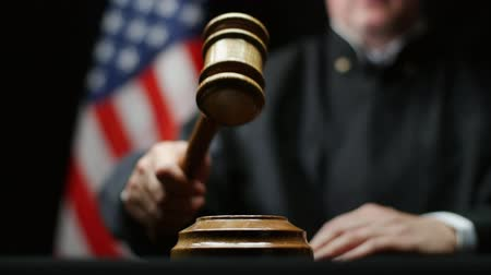 judiciary : Judge with wooden hammer in his hand against American flag in USA court room Stock Footage
