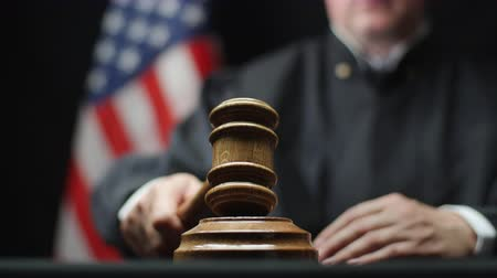 tribunal : Judges hand with wooden gavel hammering against American flag in court
