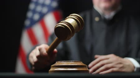 tribunal : Judges hand with wooden gavel hammering against American flag in USA court room