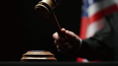 judiciary : Judges hand with wooden hammer against American flag in USA court