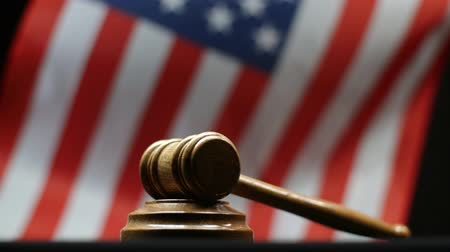 tribunal : Judges wooden gavel against American flag waving in USA court room