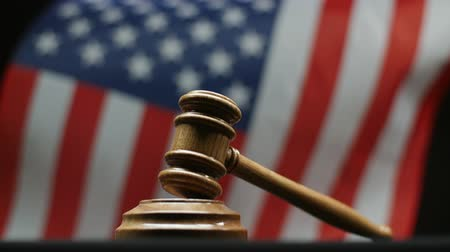 tribunal : Judges wooden gavel on block American flag waving in United States court