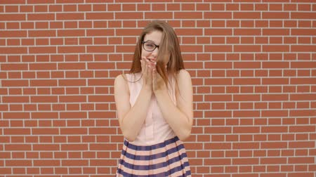 radiante : Happy girl student in glasses laughing over emotionally against a brick red wall