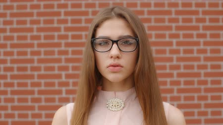 伝える : Upset girl student in glasses saying no to the camera against a brick red wall