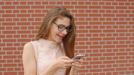 odeslat : Girl student in glasses texting messages on smartphone smiling with suprise against a brick wall