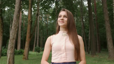 radiante : Portrait of a girl model in a good mood walking around a park, looking at trees and smiling