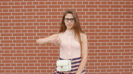 seducing : Upset girl student in glasses showing dislike sign against a brick wall background