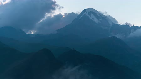 gergeti : Mystical alpine landscape. View of snow-capped peak of Mount Kazbegi, thick fog low rolling clouds