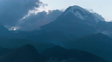 gergeti : Mystical alpine landscape. View of snow-capped peak Mount Kazbek, ravines, church on top of a hill Stock Footage