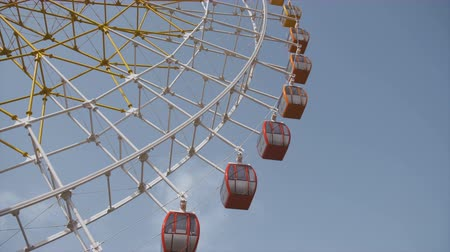 карусель : Big ferris wheel rotates at amusement park ride over clean blue sky close up