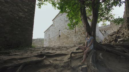 defensiva : Girl resting sitting on roots of tree in territory of ancient defensive fortress with stone masonry