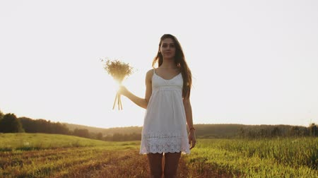 yetiştirmek : Woman in white dress standing in field with bouquet of flowers looking at camera, smiling